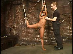Sinnamon Love tied standing on one leg, caned