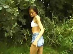 Skinny chick is giving a show in the great outdoors on grass