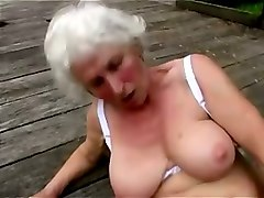 mature busty pale skin woman masturbating with a toy outside